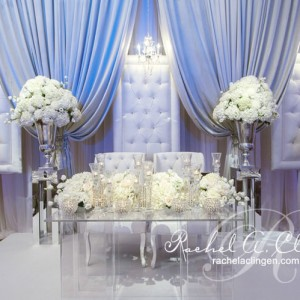 Lavish padded chairs and draped backdrop behind an elegant floral head table by Rachel A. Clingen Toronto Wedding Design and Decor